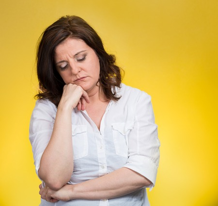 Depressed, gloomy. Closeup portrait unhappy middle age woman head on hand bothered by mistake situation having bad headache isolated yellow background. Negative human emotion facial expression feeling