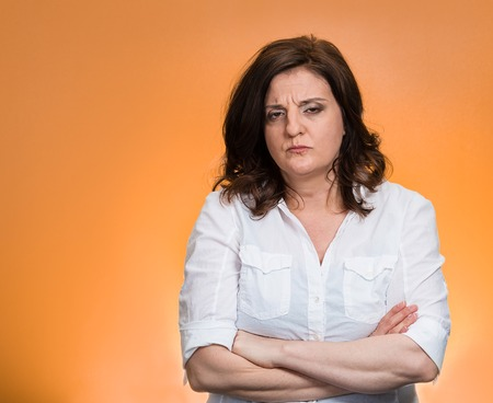 Closeup portrait displeased pissed off angry grumpy pessimistic woman with bad attitude, arms crossed looking at you, isolated orange background. Negative human emotion facial expression feeling