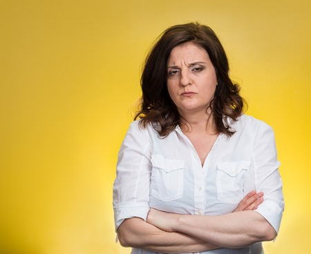 Closeup portrait displeased pissed off angry grumpy pessimistic woman with bad attitude, arms crossed looking at you, isolated yellow background. Negative human emotion facial expression feeling Stock Photo
