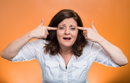 Closeup portrait angry mad middle aged woman gesturing with fingers against temple asking are you crazy? Isolated orange background. Negative human emotions facial expression feeling body language Stock Photo