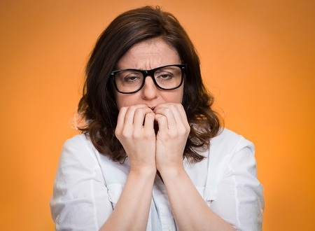 Closeup portrait headshot nervous, stressed middle aged woman with glasses biting fingernails looking anxiously, craving for something isolated orange background. Human emotion face expression feeling photo