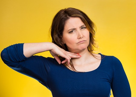 cut off head: Cut it out all nonsense. Portrait angry woman gesturing to stop talking or she will take your head off isolated yellow background. Negative emotion face expression bad feeling non verbal communication Stock Photo