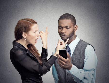 scandal: Upset angry woman trying to bring attention of young handsome man ignoring her looking at smartphone reading browsing internet isolated grey wall background. Phone addiction concept. face expression