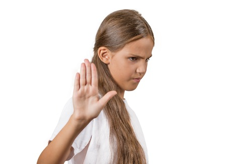 Closeup portrait grumpy teenager girl with bad attitude giving talk to hand gesture with palm outward, isolated white background. Negative emotions, facial expression feelings, body language reaction