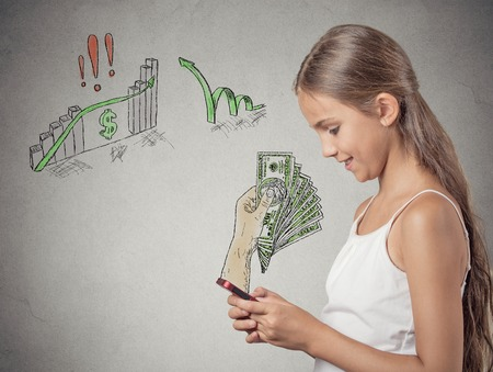 cash back: business on a go. Teenager girl working online on smart phone making earning money, hand with dollar bills banknotes reward coming out of phone screen isolated grey background. Human face expression Stock Photo