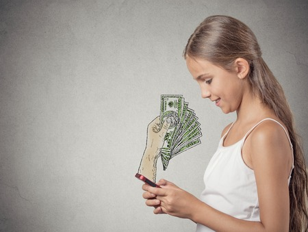 coming out: business on a go. Teenager girl working online on smartphone making earning money, hand with dollar bills banknotes coming out of phone screen, isolated grey wall background. Human face expression