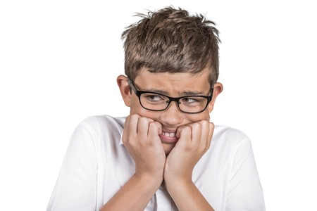 perfectionist: Closeup portrait headshot nervous anxious stressed boy with eyeglasses biting fingernails looking anxiously craving something, afraid isolated white background. Negative emotion facial expression