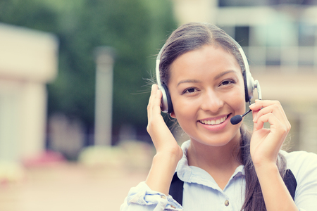 Closeup portrait smiling young female customer service representative call center agent support staff operator with phone headset isolated background with trees city building. photo