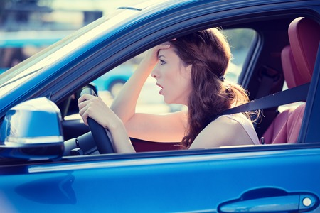 frustration girl: Side view window portrait displeased stressed angry pissed off woman driving car annoyed by heavy traffic isolated street background. Stock Photo