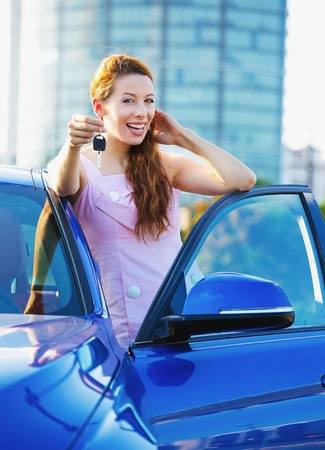 car sales: Portrait happy smiling young attractive woman buyer standing next to new blue car showing keys  Stock Photo