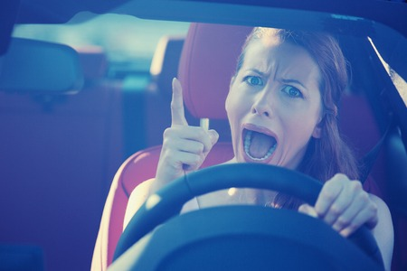 Portrait displeased angry pissed off aggressive woman driving car photo