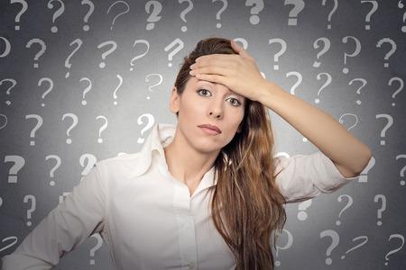 Portret benadrukte vrouw met hoofdpijn heeft veel vragen geïsoleerd grijze muur achtergrond met vraagtekens. Stockfoto