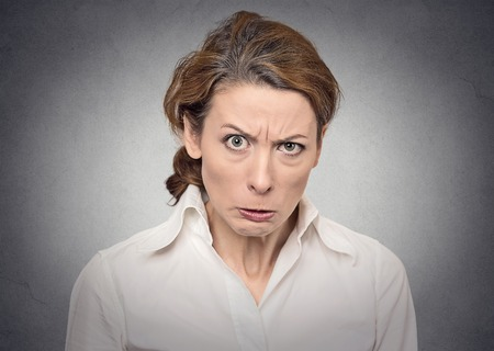 bitchy: portrait angry woman on grey background Stock Photo