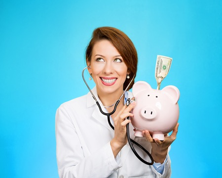 time deficit: Closeup portrait health care professional doctor nurse listening with stethoscope to piggy bank, dollar bill isolated blue background.