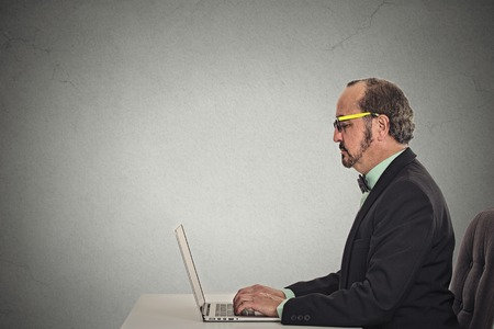 siting: Side view profile corporate man with glasses using his laptop isolated grey wall background. Middle aged executive working on computer, siting at office desk. Face expression. Internet network