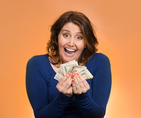 cash back: Closeup portrait super happy excited successful middle aged business woman holding money dollar bills in hand isolated orange background.