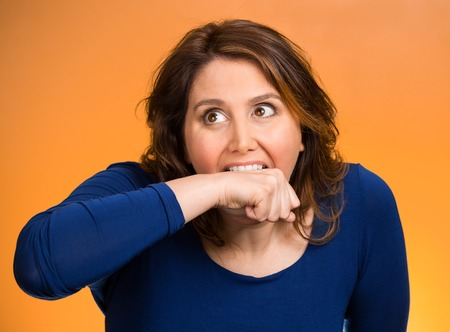 obsessive compulsive: Closeup portrait headshot crazy angry loony middle aged business woman worker employee going nuts through stress conflict in life biting her arm isolated orange background.