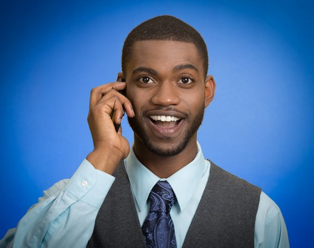Headshot portrait happy business man young guy talking on mobile phone smiling isolated on blue background.  photo