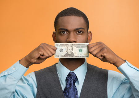 under paid: Portrait handsome corrupt guy businessman holding twenty dollar bill to mouth silent avoiding truth isolated orange background.