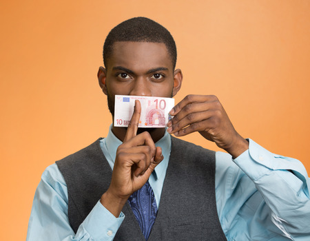 Portrait handsome corrupt guy businessman holding euro bill to mouth showing shhh sign finger to lips isolated on orange background.