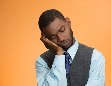 inattentive: Closeup portrait sleepy young business man, funny guy placing head on hand, unhappy, eyes closed, isolated orange background. Stock Photo