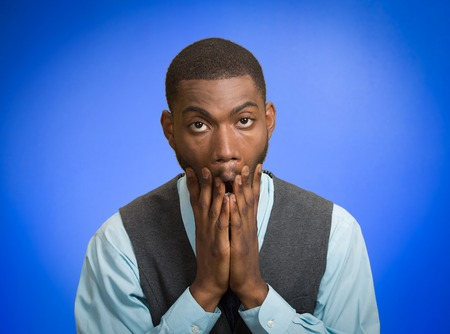 Closeup portrait, headshot young tired, fatigued business man worried, stressed, dragging face down with hands, isolated blue background. photo