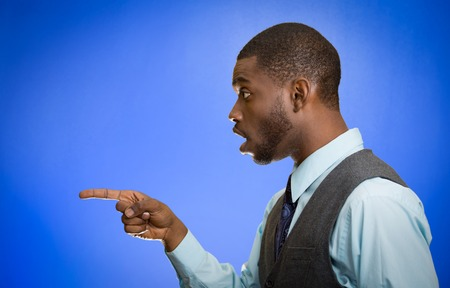 side profile: Closeup side view profile portrait handsome young man pointing index finger at something stunned dumbstruck looking at someone gesture isolated blue background.