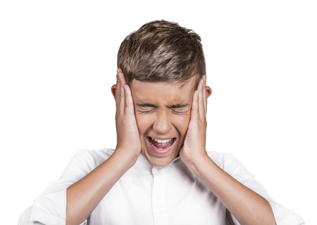 people problems: Closeup portrait stressed, frustrated, teenager boy annoyed by loud noise having panic attack screaming isolated white background.