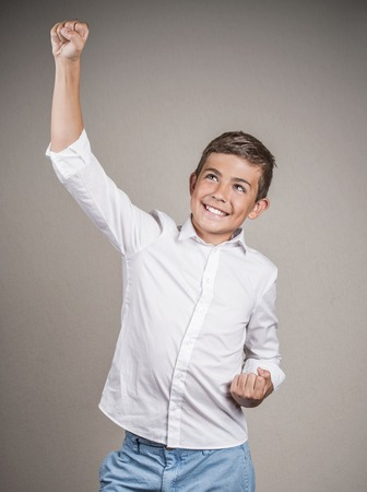 enrolled: Portrait happy successful student fists pumped celebrating success isolated grey background.