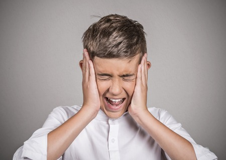 loud noise: Closeup portrait stressed teenager boy annoyed by loud noise having panic attack screaming isolated grey background.