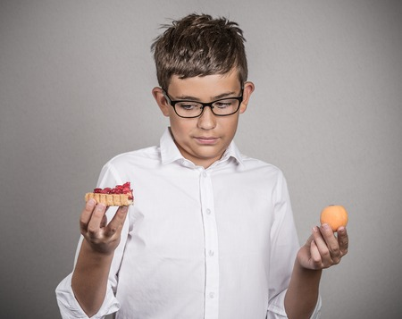 metabolic: Closeup portrait young man with glasses deciding on diet, making choice sweet cookie tart fresh fruit apricot isolated grey background.