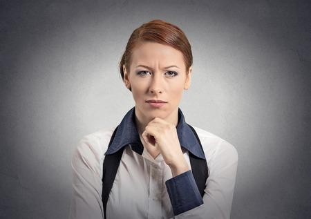 desconfianza: Escéptico mujer dudoso que le mira la cámara aislada fondo de la pared gris.