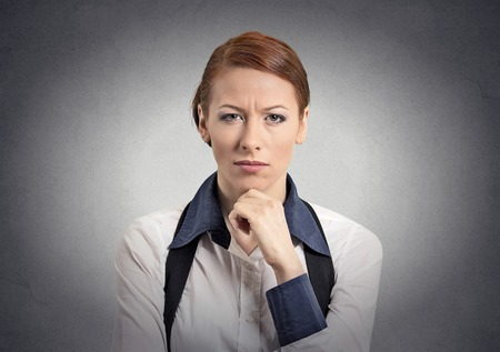 cynical: Skeptic doubtful woman looking at you camera isolated grey wall background.