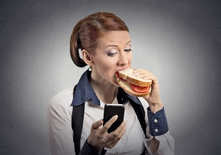 obsession: Closeup portrait young serious corporate business woman deal maker reading news message on smart mobile phone holding eating sandwich isolated grey background.