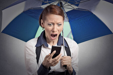 cell phone addiction: Closeup portrait shocked surprised business woman corporate executive reading bad breaking news on smart phone holding umbrella protected from rain isolated grey background.