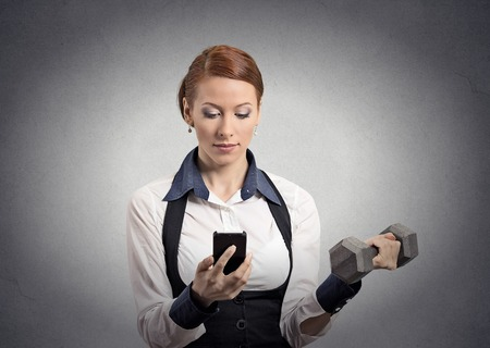 Closeup portrait strong business woman reading news on smart phone, holding mobile, lifting weight dumbbell isolated grey wall background.  photo