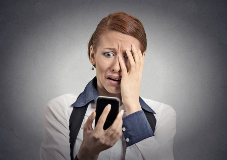 inappropriate: Upset stressed woman holding cellphone disgusted shocked with message she received isolated grey background.