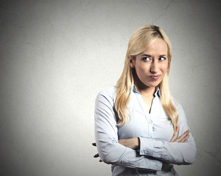 insidious: Portrait displeased pissed off angry grumpy young woman bad attitude arms crossed looking sideways at copy space isolated grey wall background. Stock Photo