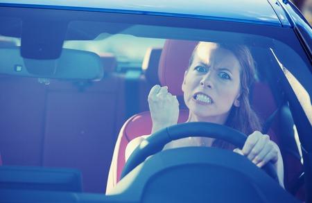 Portrait déplut colère voiture énervé femme conduite agressive, criant à quelqu'un dans le trafic de poing de la main en vue de pare-brise avant de l'air. Banque d'images - 32554750