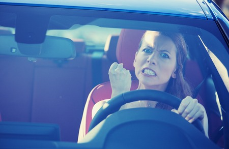 Portrait displeased angry pissed off aggressive woman driving car, shouting at someone in traffic hand fist up in air front windshield view.