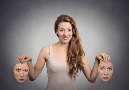 doubt: portrait beautiful happy girl holds two masks isolated grey wall background. Human face expressions, emotions, feelings, bipolar state of mind concept