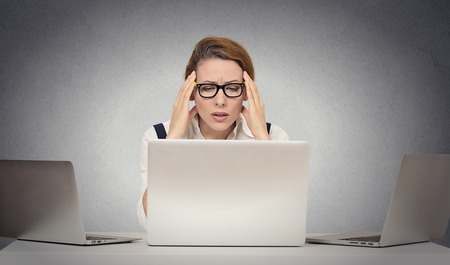 failed: Depressed tired unhappy business woman siting at desk in front of many laptop looking gloomy isolated office grey wall background with copy space.