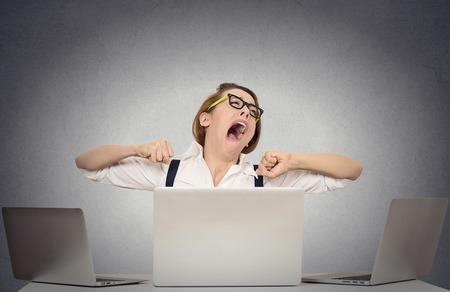 femme bouche ouverte: Portrait d'affaires béant endormi femme avec de grands yeux bouche ouverte fermée l'air de s'ennuyer assis à son bureau avec des ordinateurs isolés mur gris de bureau fond.