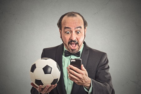 Portrait excited man looking shocked with opened mouth on cell smart phone watching game holding football isolated grey wall background.  photo