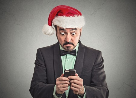 kwanzaa: Portrait surprised funny business man wearing red santa claus hat looking at smart phone shocked discovered great online deal sale.  Stock Photo