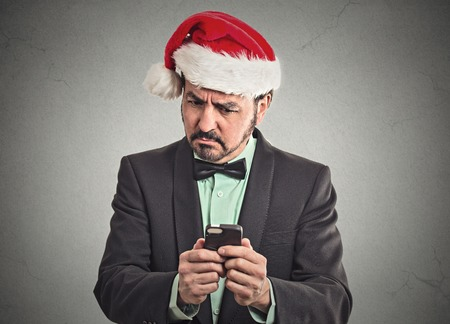 business skeptical: Portrait surprised skeptical funny business man wearing red santa claus hat looking at smartphone discovered online deal to good to be true.