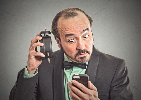 surprised man with alarm clock looking at his smart phone with confused face expression isolated grey wall background photo