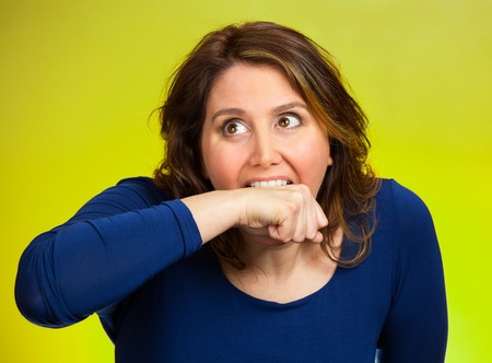 obsessive compulsive: Closeup portrait headshot crazy angry loony middle aged business woman worker employee going nuts through stress conflict in life biting her arm isolated green background.