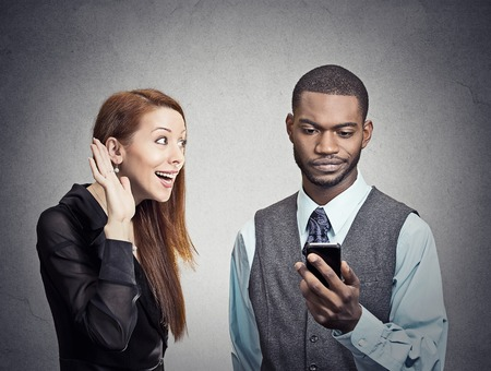 Attractive woman trying to bring attention of young handsome man ignoring her looking skeptical at smartphone reading browsing internet grey wall background.