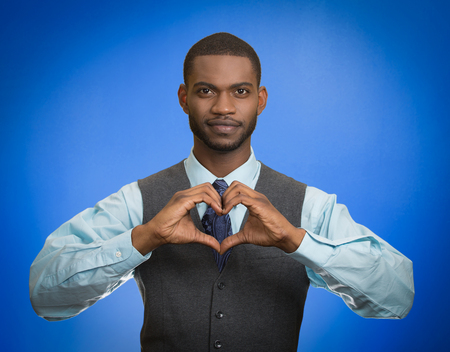 Portrait handsome smiling young business man makes hands shaped like heart using fingers isolated on blue background.  photo
